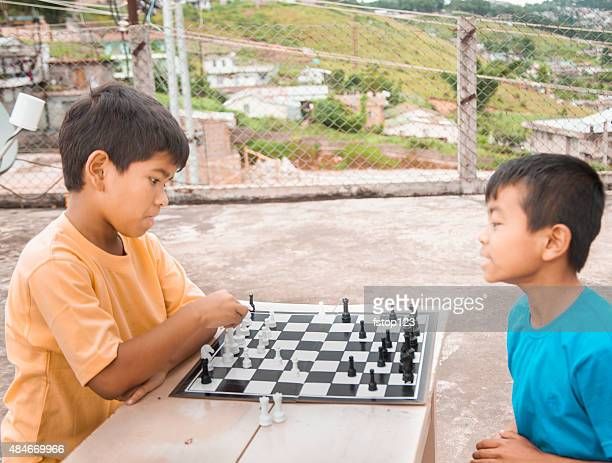 Boys, friends playing a game of chess. Children. Urban setting.