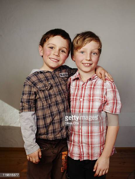 2 boys / friends standing arm in arm