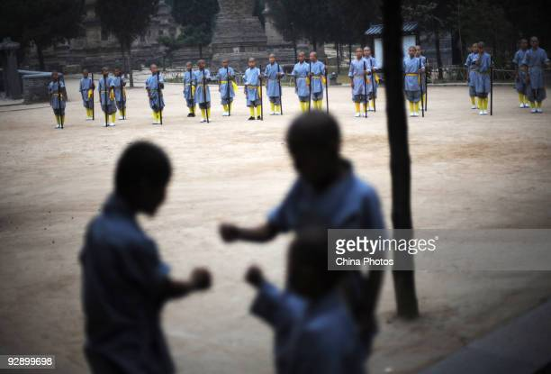 Boys from Shaolin Kung Fu Training Base practice Kung Fu movements at the Shaolin Temple on the Songshan Mountain on October 30, 2009 in Dengfeng of...