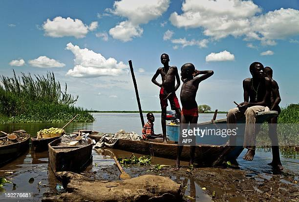 Boys from the Mandari tribe wait by the Nile river for boats with the day's catch to arrive in Terekeka a fishing community 75km north of Juba in...