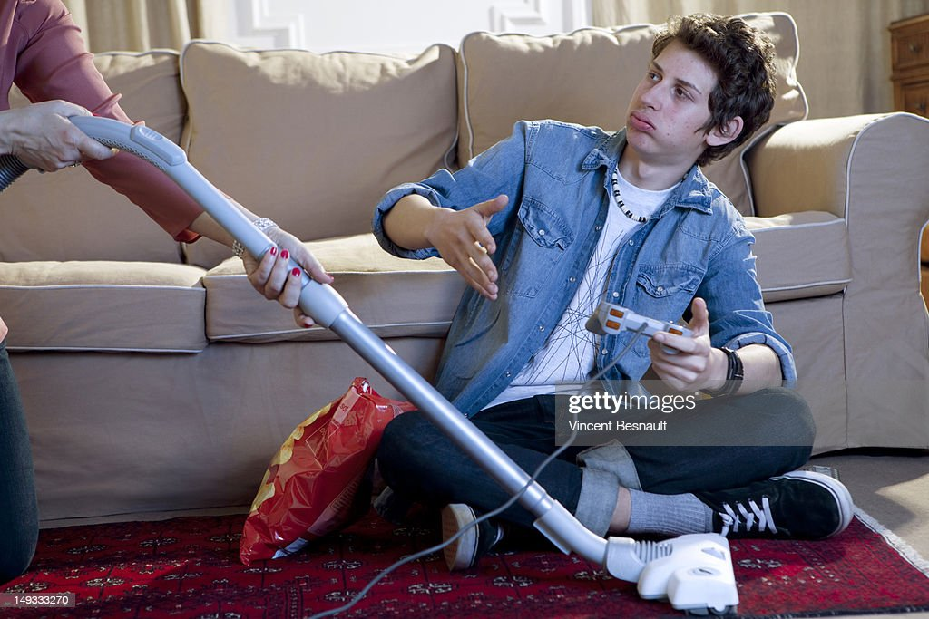 A boy's gaming interrupted by his mum's vacuuming : Stock-Foto