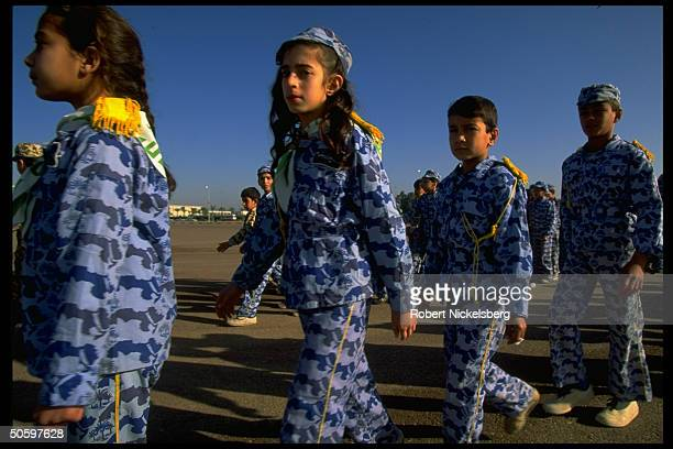 Boys & girls in quasi-mil. Scout-type uniforms marching , prob. During Army Day fete for 73rd anniv. Of formation of Iraqi Army.