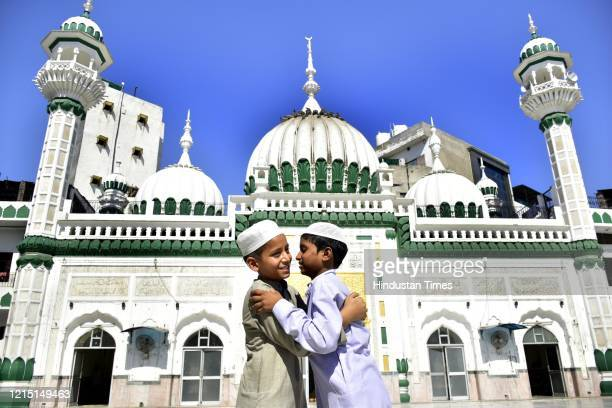 Boys greet each other after offering prayers at Khairudeen Mosque on the occasion of Eid ulFitr on May 25 2020 in Amritsar India