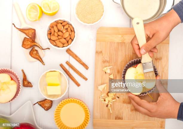 boys hand coating apple half with lemon juice - basting brush stock photos and pictures