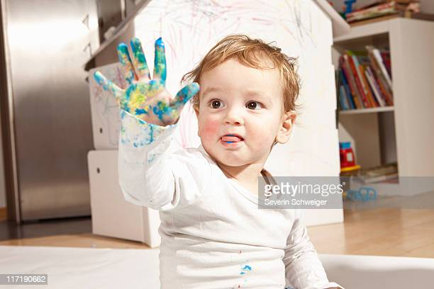Boys hand covered with finger paint