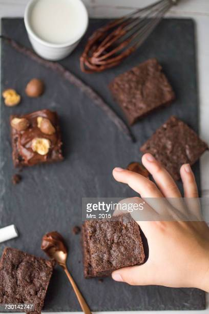 boys hand reaching for a chocolate brownie - brownie stock pictures, royalty-free photos & images