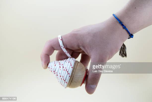 boy's hand wrapped with the string of a spinning top