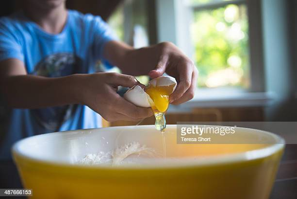 Boy's Hands Cracking an Egg Into Bowl