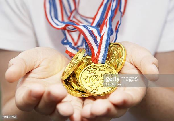boys hands held out full of gold medals - medalist stock pictures, royalty-free photos & images