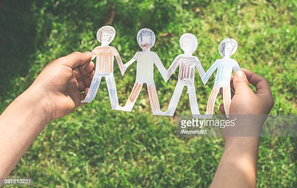 Boys hands holding chain of painted paper figurines in front of a meadow