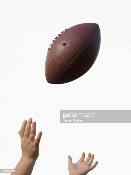 Boy's hands reaching to catch American football