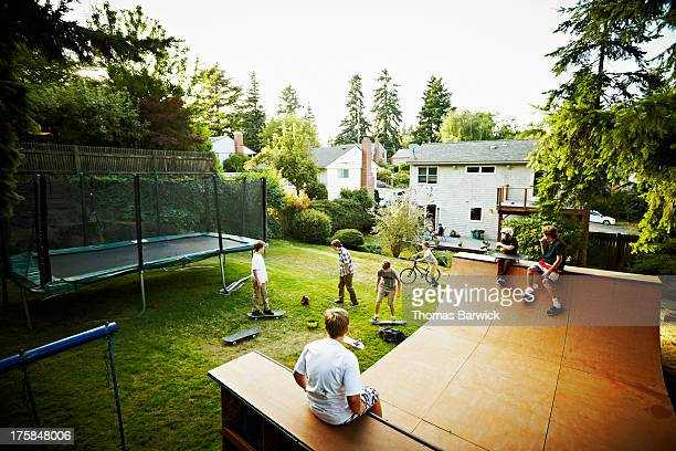 boys hanging out and playing in backyard of home - half pipe stock pictures, royalty-free photos & images