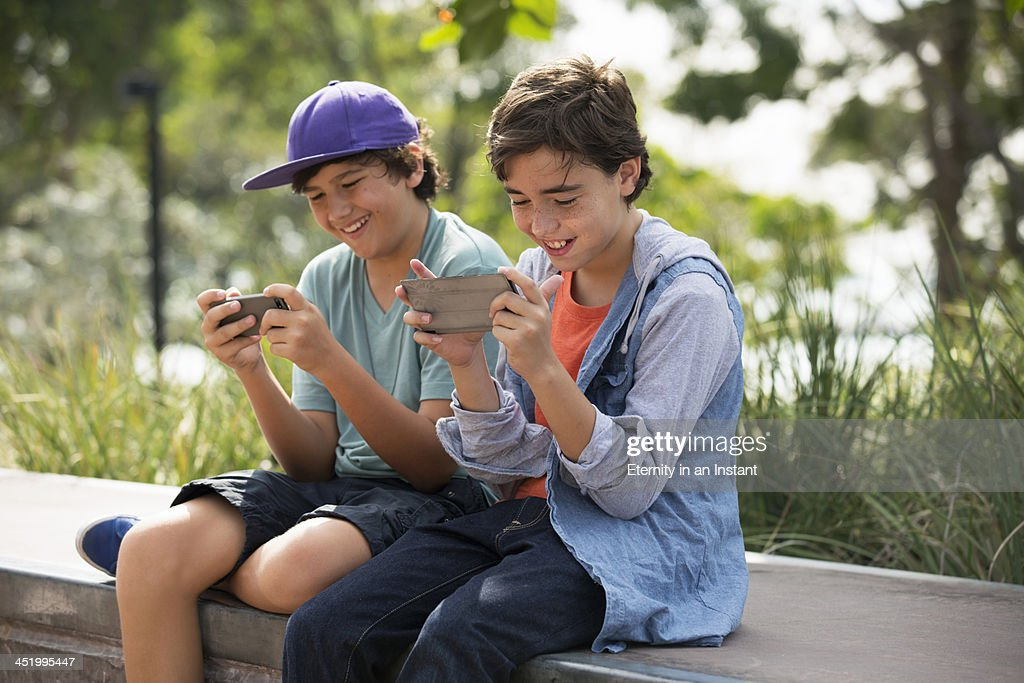 Boys hanging out playing games on their phones. : Stock Photo