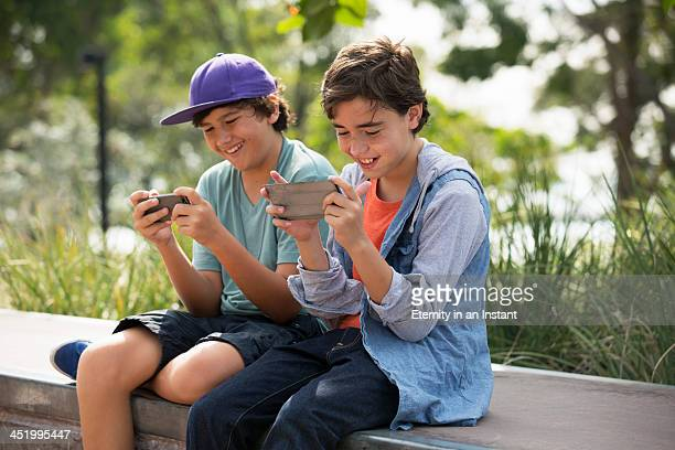 Boys hanging out playing games on their phones.