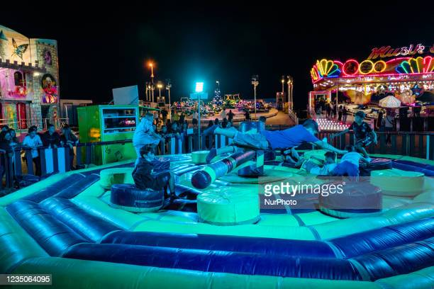 Boys have fun jumping over the rotating obstacle on the first day of the Luna Park opening in Molfetta on 4 September 2021. On the occasion of the...