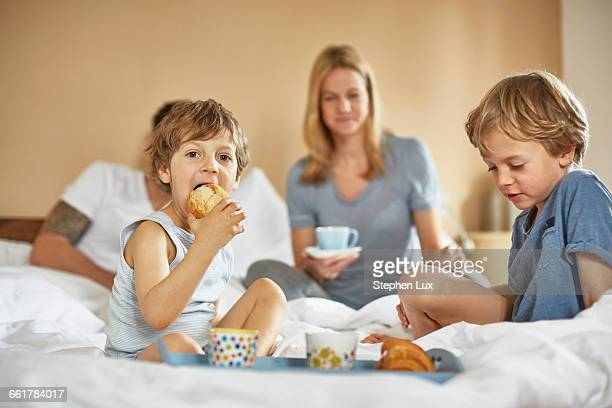boys having breakfast in parents bed - breakfast in bed stock pictures, royalty-free photos & images