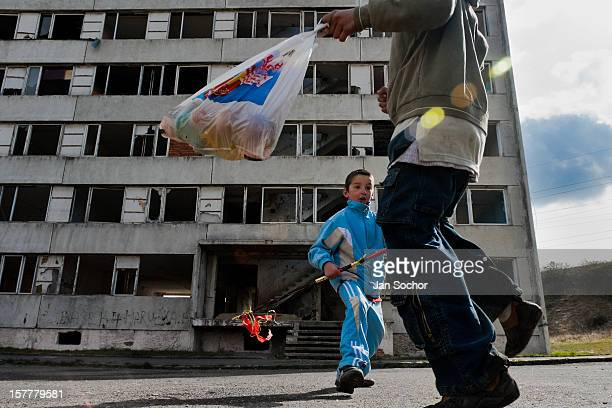 Boys having their bag full of Easter eggs happily dance in front of a devastated apartment block in the Gipsy ghetto of Chanov Most Czech Republic 26...