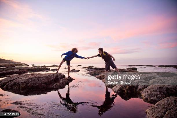Boys help each other across tidal pools at sunset