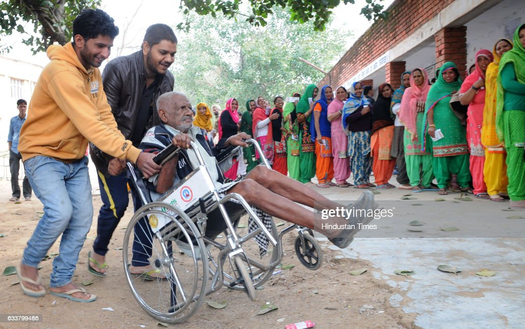 Boys helping a voter at a polling station during Punjab election at Nada village on February 4 2017 in Kharar India Punjab on Saturday voted in its...