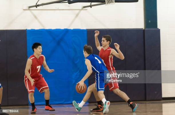 boys high school basketball game - charging sports stock photos and pictures