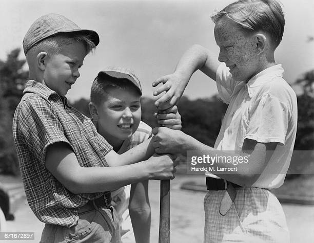 boys holding and looking at baseball bat - {{relatedsearchurl(carousel.phrase)}} fotografías e imágenes de stock