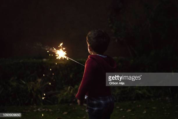 boys holding spraklers for new year's eve - mexican christmas stock photos and pictures
