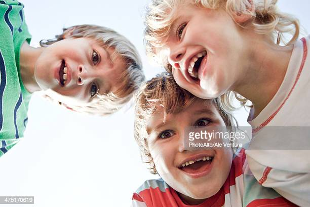 Boys huddling, smiling down at camera