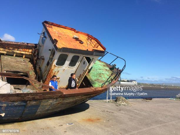 Boys In Abandoned Boat On Pier Against Blue Sky