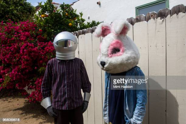 boys in backyard wearing space helmut and bunny mask - bizarre stock pictures, royalty-free photos & images