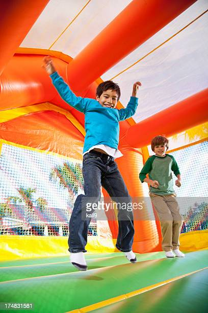 boys in bounce house - bouncing stock pictures, royalty-free photos & images