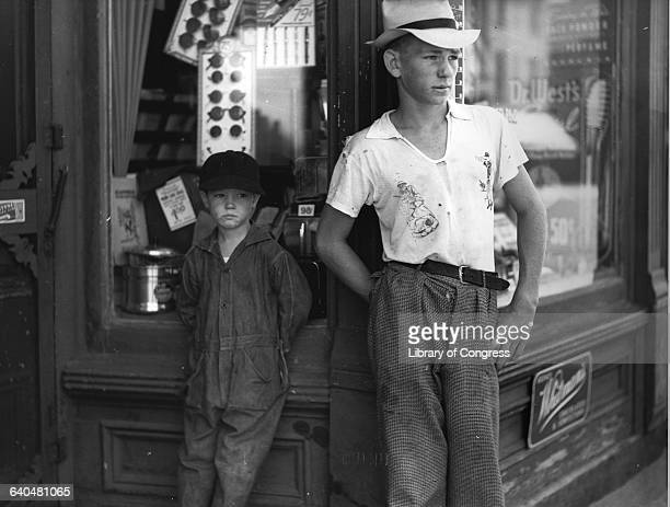 Boys in Dover Delaware stand in front of a drugstore watching the world go by