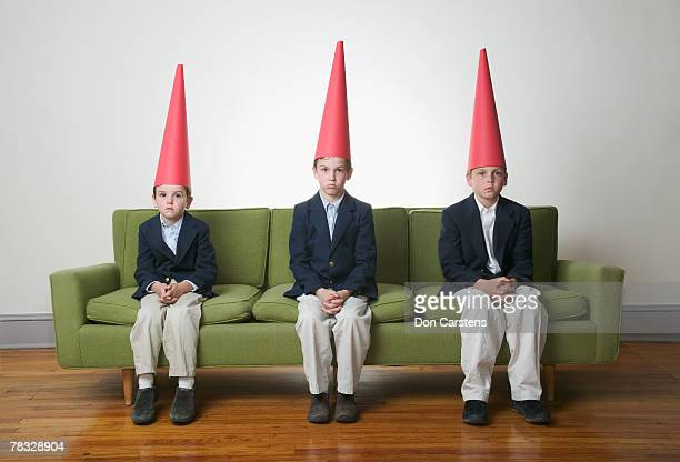 boys in dunce caps - dunce's hat stock pictures, royalty-free photos & images