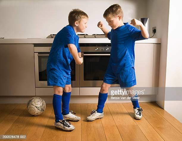 Boys (8-10) in football strip flexing muscles in kitchen