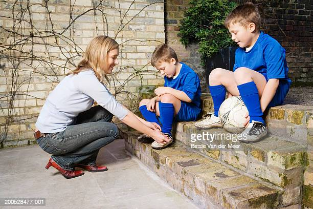 Boys (8-10) in football strip having shoes tied by mother