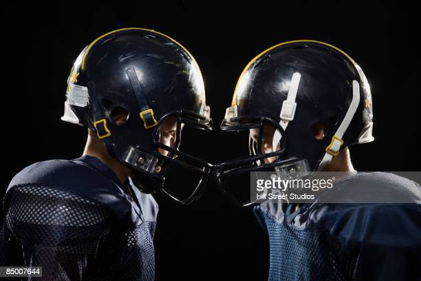 boys in football uniforms - football helmet stock pictures, royalty-free photos & images