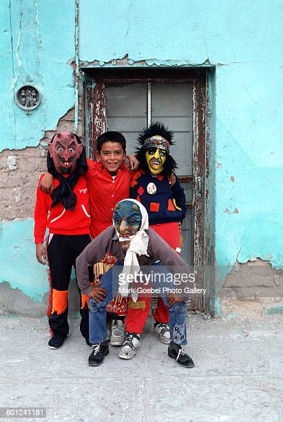 Boys in Halloween costumes clown about in front of a light blue, adobe building, Juarez, Mexico, late 1980s.