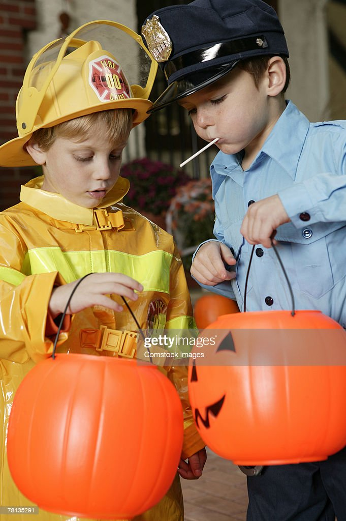 Boys in Halloween costumes eating candy : Stock Photo