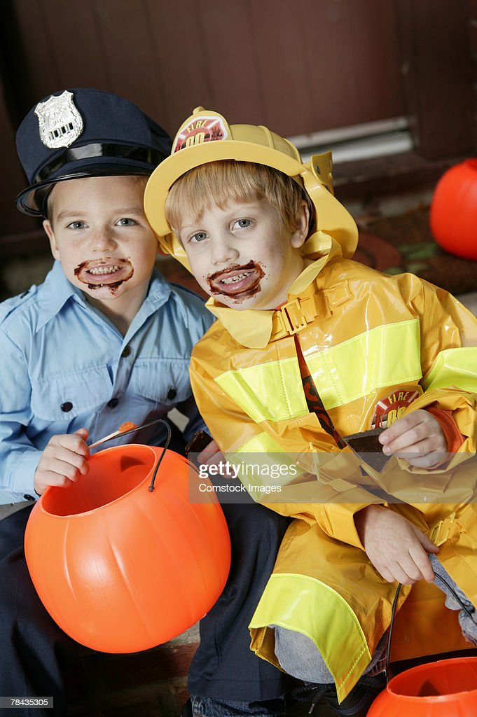 Boys in Halloween costumes with chocolate on faces : Stockfoto