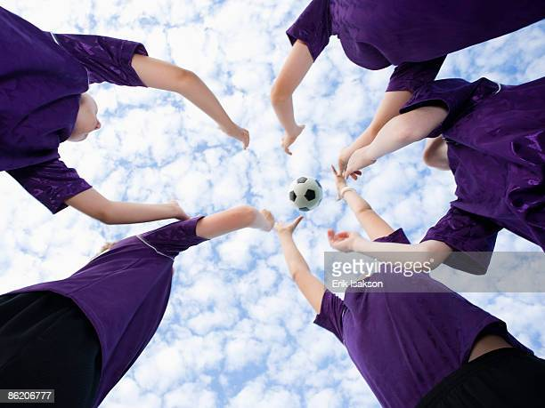 Boys in huddle throwing soccer ball in air