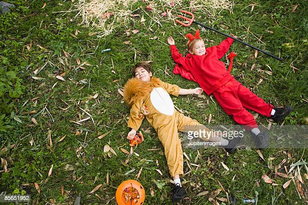 Boys in lion and devil costumes lying down in grass