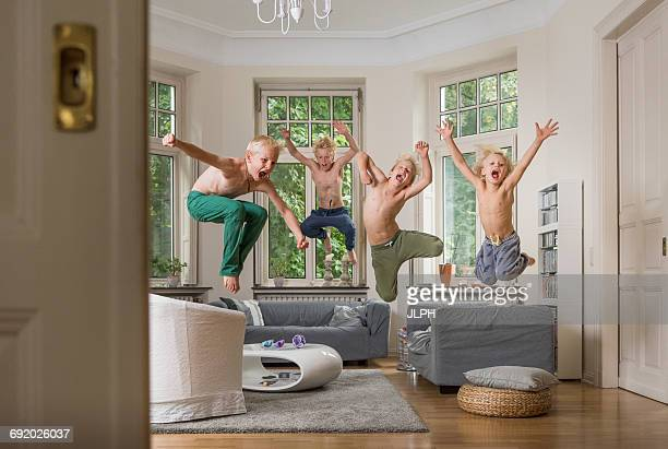 Boys in living room jumping in mid air