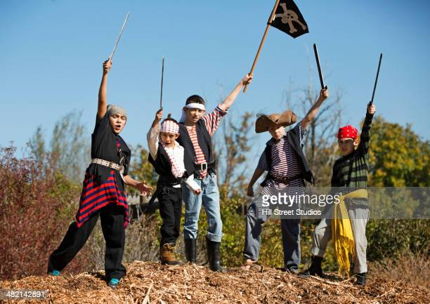 Boys in pirate costumes holding swords and flag