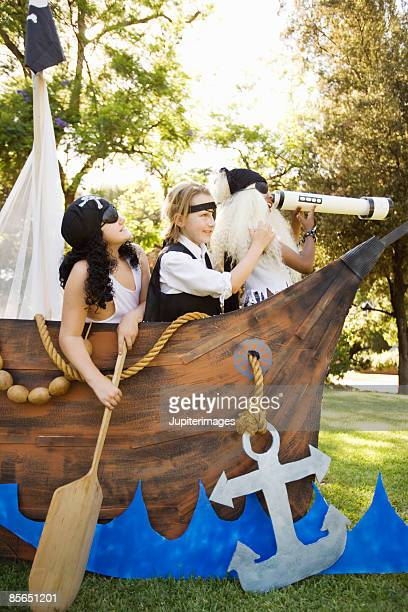 Boys in pirate costumes playing in boat