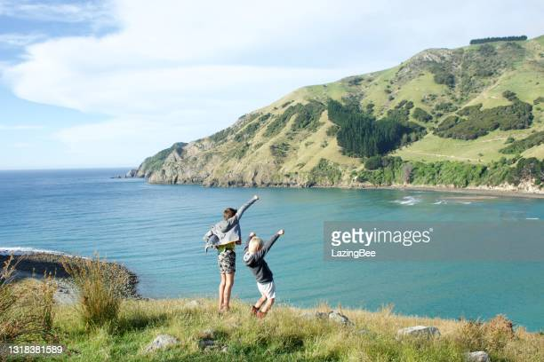 boys in rural coastal landscape with hands in the air - local landmark stock pictures, royalty-free photos & images