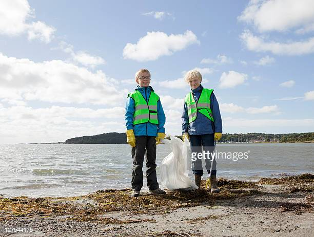 boys in safety vests cleaning beach - västra götaland county stock pictures, royalty-free photos & images