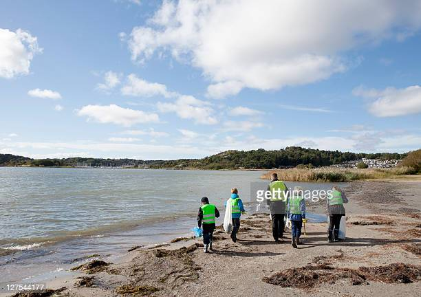 boys in safety vests cleaning beach - environmentalist stock pictures, royalty-free photos & images