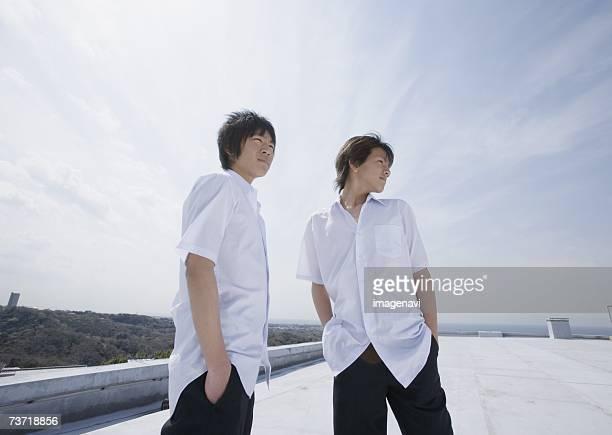 Boys in school uniform standing on rooftop