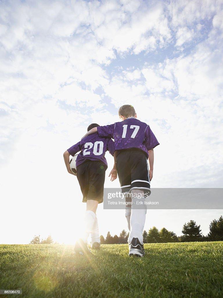 Boys in soccer uniforms walking on field : Stock Photo