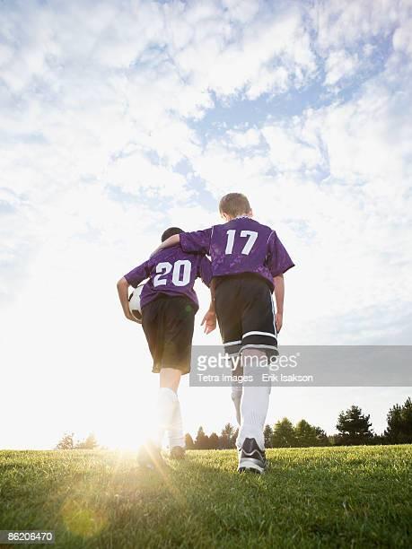 Boys in soccer uniforms walking on field