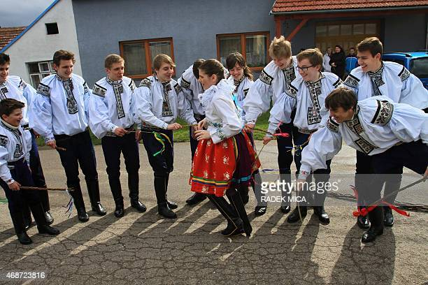 Boys in traditional dresses symbolically beat a girl with small whips during a traditional Easter festivity on Easter Monday April 6 in the village...